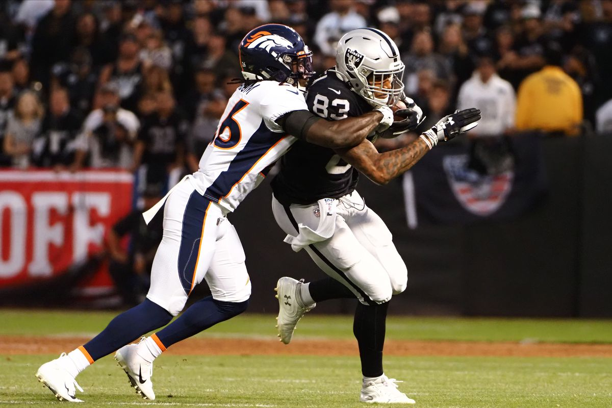 Oakland Raiders tight end Darren Waller carries the ball against Denver Broncos cornerback Isaac Yiadom during the first quarter at Oakland Coliseum.