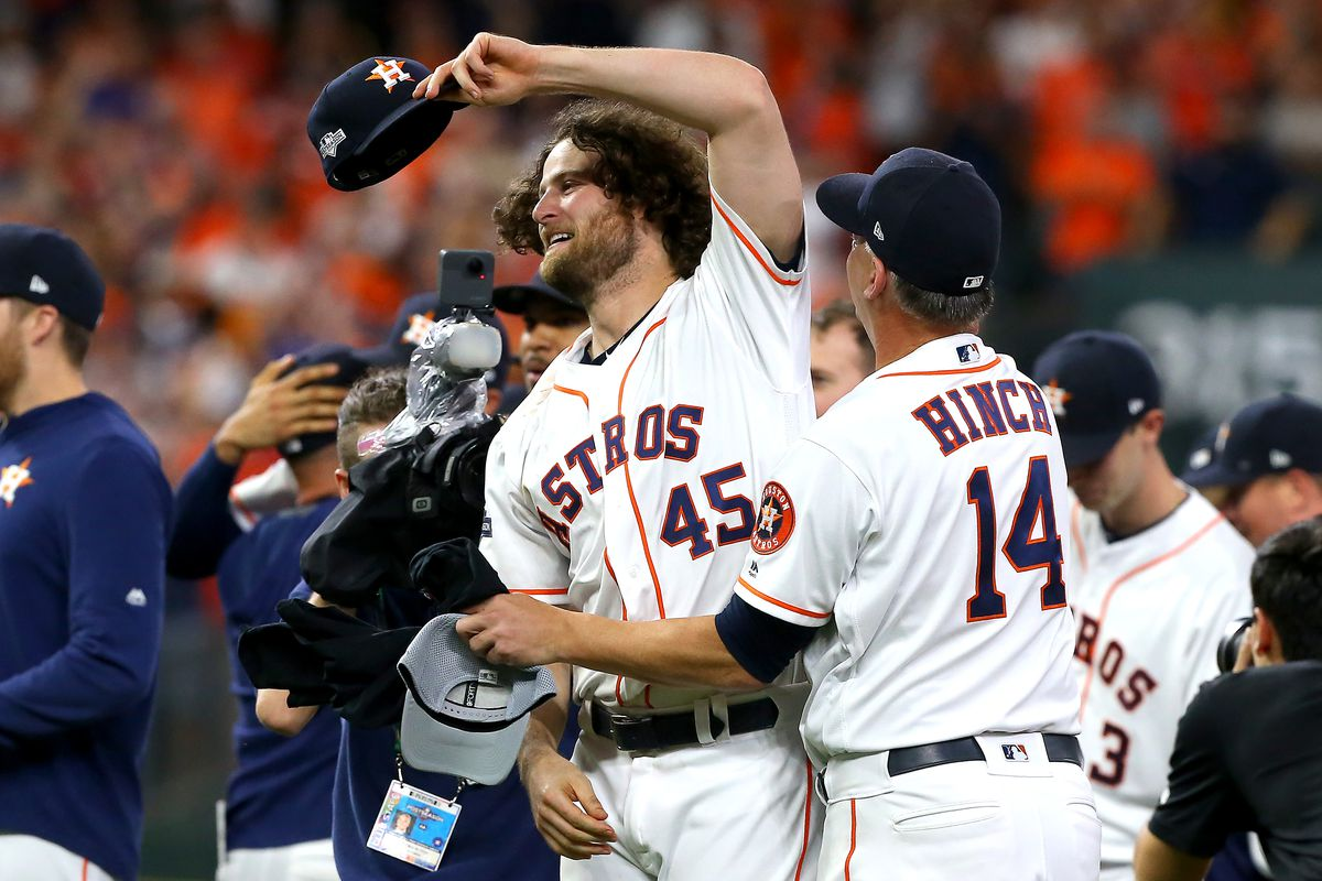 Gerrit Cole #45 and AJ Hinch #14 of the Houston Astros embrace after their teams 6-1 win over the Tampa Bay Rays in game five of the American League Division Series at Minute Maid Park on October 10, 2019 in Houston, Texas.