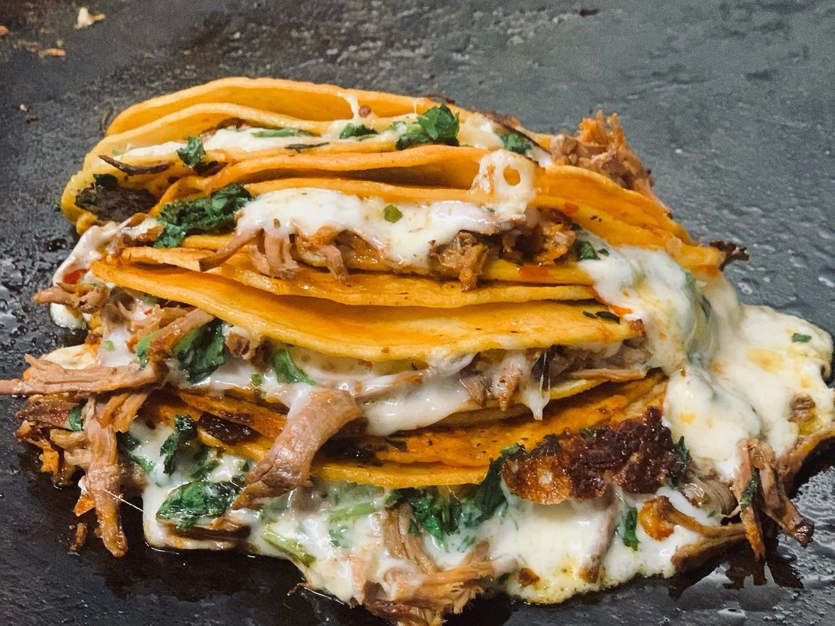 A pile of tacos with cheese, meat, and cilantro on top of a black griddle