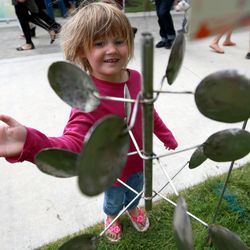 Madison Van Valer spins a Spin Mills sculpture, by Mike Merback, at the Downtown Farmers Market at Pioneer Park in Salt Lake City on Saturday, June 14, 2014.