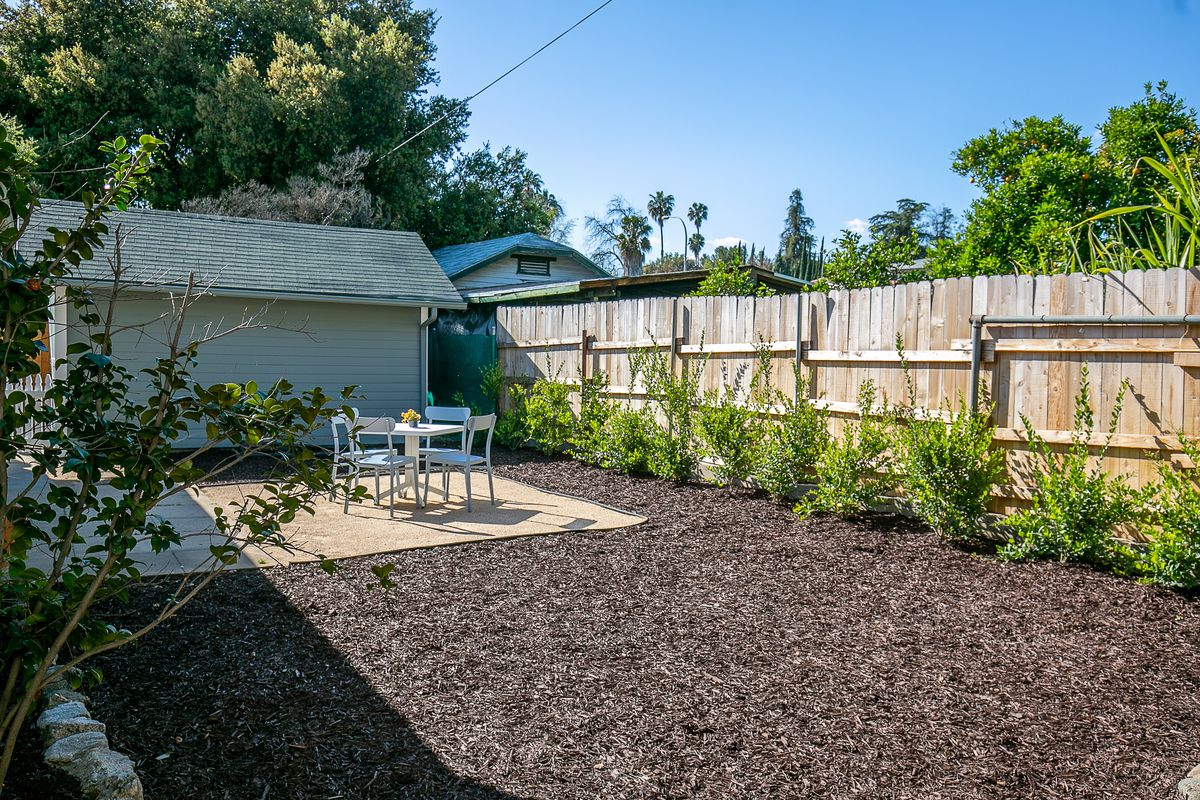 A yard with woodchips and a wooden fence. A table and chairs are arranged in the middle