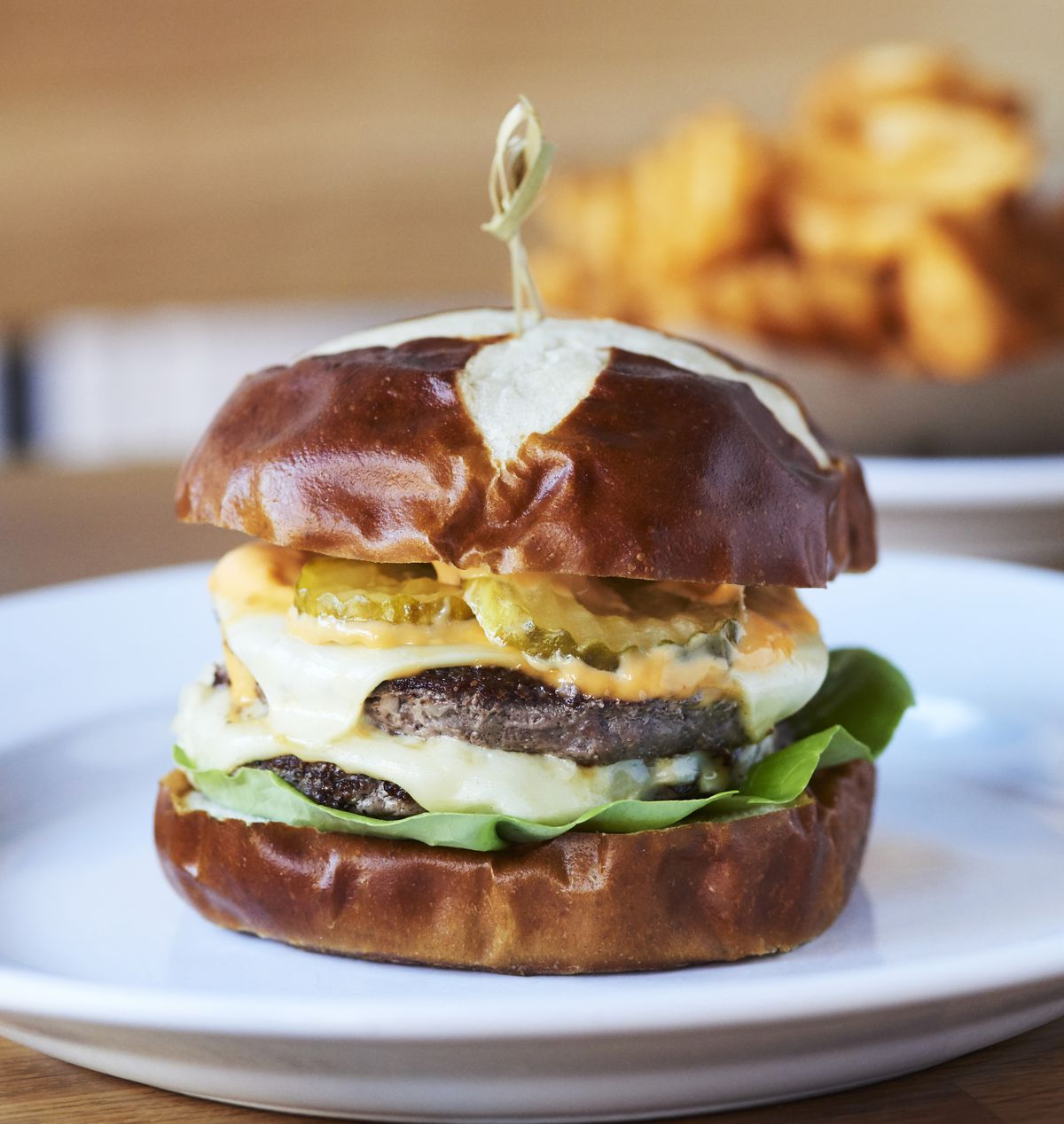 Double stack cheese burger Le Big Matt served on a pretzel bun topped with melted Amercian cheese, pickle chips and lettuce on the bottom
