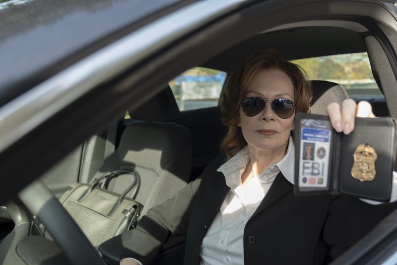 Jean Smart holding up a badge in her car.