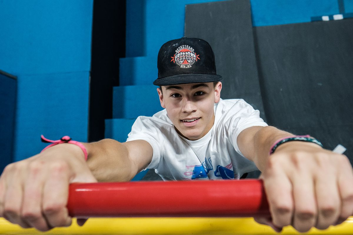 """Kai Beckstrand hangs from a bar some 25-feet up a curved wall as he demonstrates parts of his training regimen at his family's gym in St. George on Saturday, August 28, 2021. Beckstrand's efforts landed the 15-year-old in the finals on the competition television show """"American Ninja Warrior."""""""