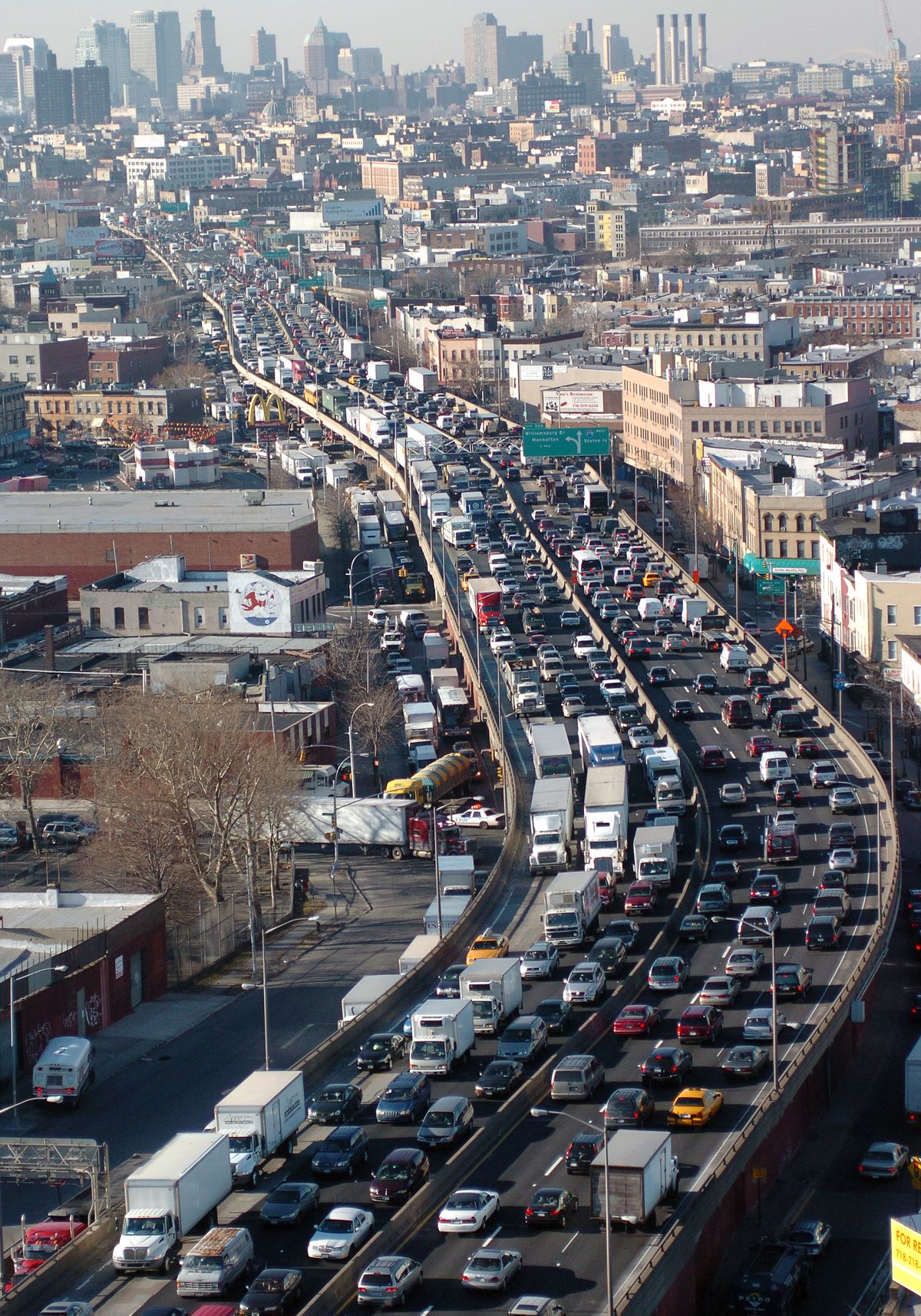 An aerial view of the Sunset Park portion of the Brooklyn Queens Expressway packed with bumper to bumper car and truck traffic. The traffic jam seems to stretch on for miles in the background.