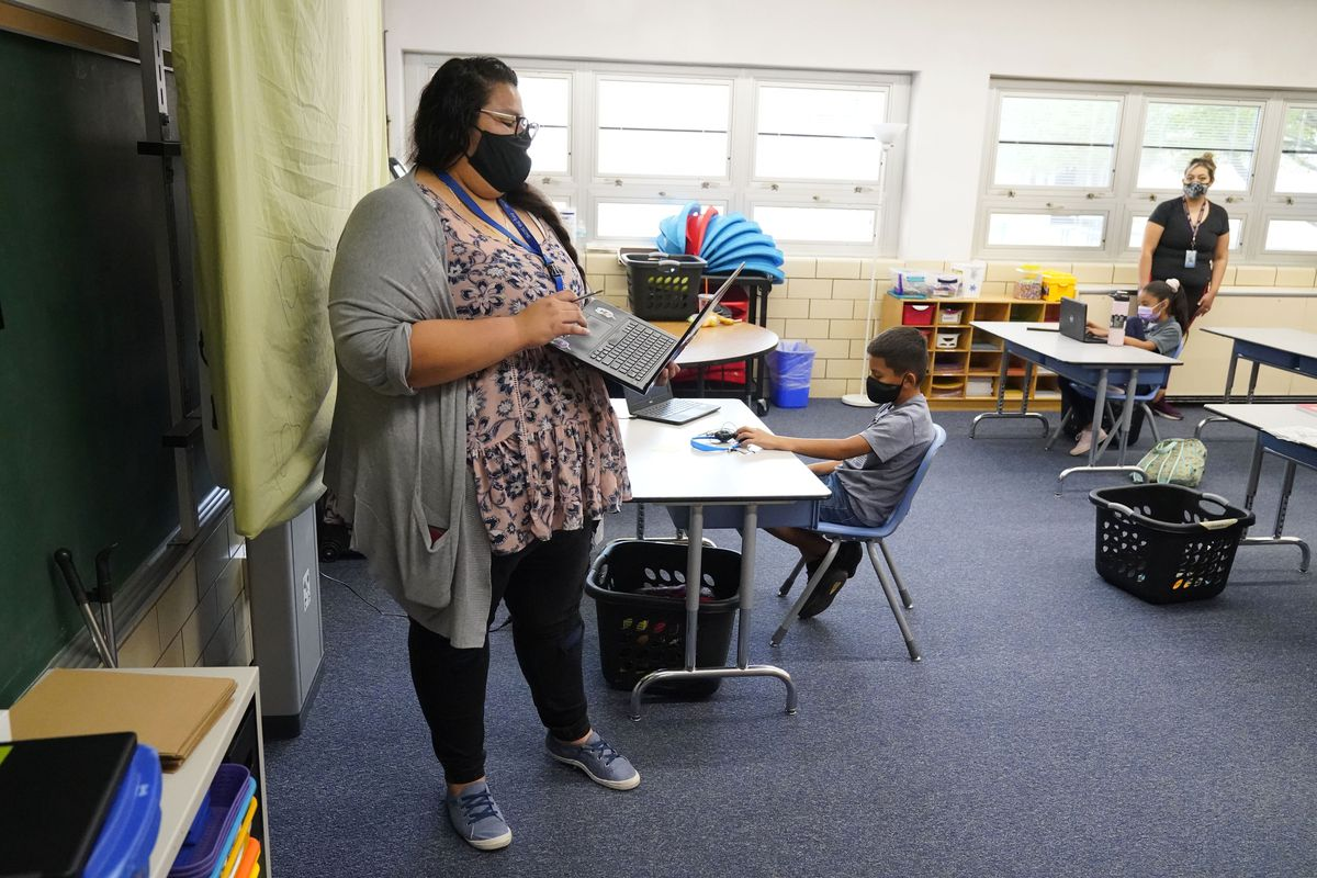Teacher wearing a mask supervises students at a learning center.