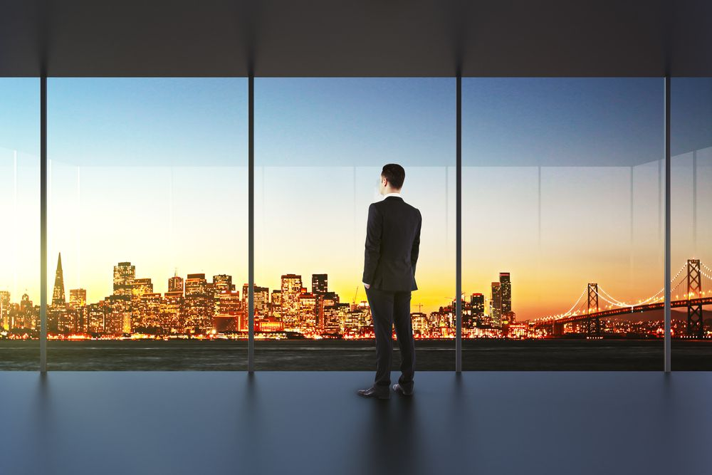 Rendering of a man standing in an empty office looking out at the San Francisco skyline.