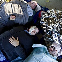 Brian Hahn (center) and Hilary Olson (bottom right) pose as victims in Centerville, Utah as part of a mock disaster on Saturday.