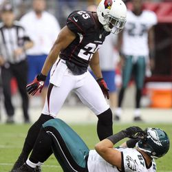Arizona Cardinals free safety Kerry Rhodes, top, stands over Philadelphia Eagles tight end Brent Celek, bottom, after jarring the ball away from Celeck in the second quarter of an NFL football game on Sunday, Sept. 23, 2012, in Glendale, Ariz.