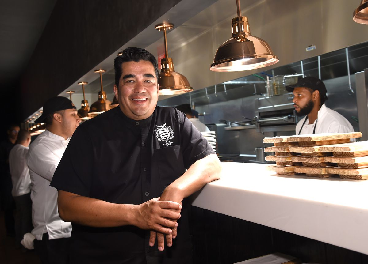 Chef Jose Garces standing at the lip of an open kitchen while wearing a black chef's coat.