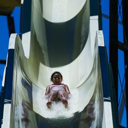 Aliana Bravo, 9, slides down a slide at Seven Peaks Waterpark in Salt Lake City on Sunday, June 18, 2017. Pools and waterparks may be the place to be this week as temperatures are expected to approach 100 degrees along the Wasatch Front.