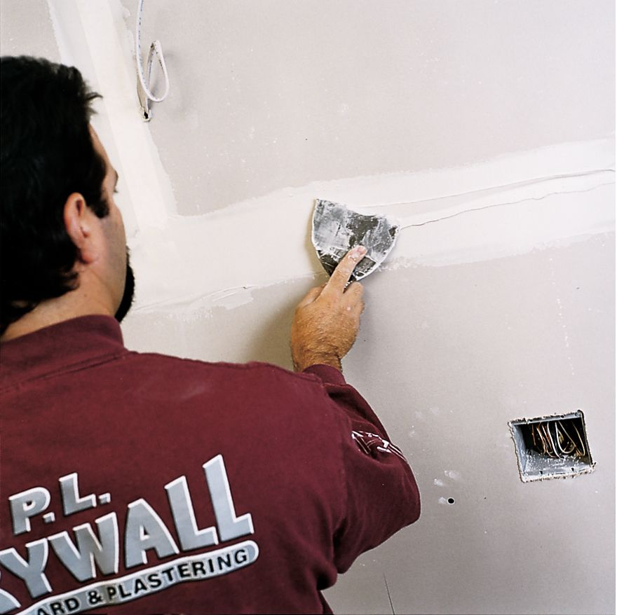 Man Covers Joints And Screwheads With Compound With Putty Knife To Finish Drywall