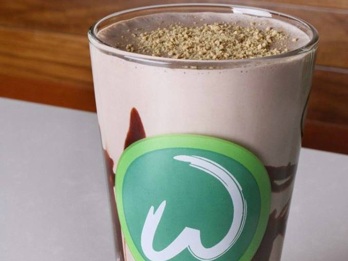 """Closeup of a chocolate frappe with a chocolate syrup swirl. There's a green circle on the glass with a white """"W"""" in it."""