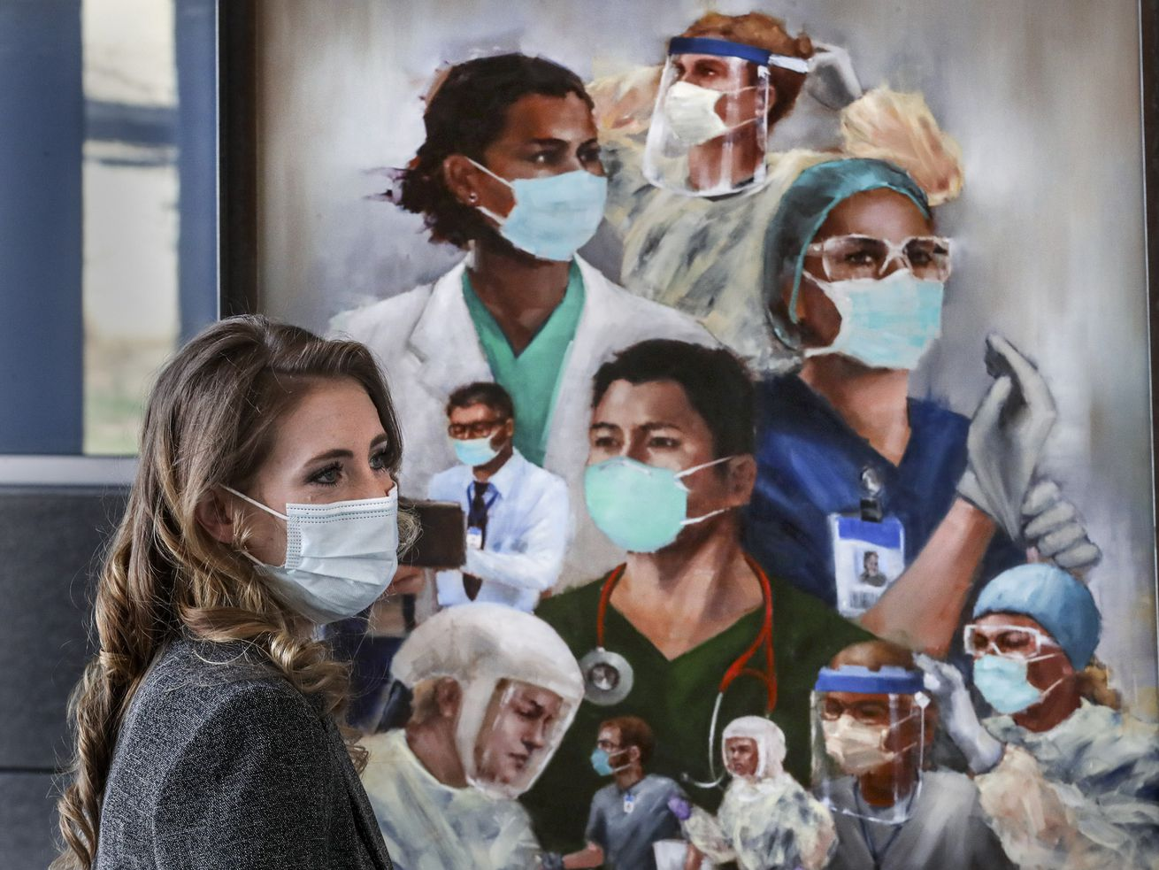 "Utah artist Heather Olsen stands with her painting, ""Together We Can Do This,"" as it is presented to caregivers at the Intermountain Transformation Center in Murray on Monday, April 5, 2021. Olsen painted the work to honor Utah caregivers for their dedication, commitment,, and heroics in saving countless lives during the pandemic. Copies of the painting will be displayed in Intermountain hospitals across the state."