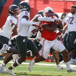 Utah running back TJ Pledger, right, runs past Washington State defenders while getting pressured during an NCAA college football game at Rice-Eccles Stadium on Saturday, Sept. 25, 2021 in Salt Lake City. Utah won the game 24-13.