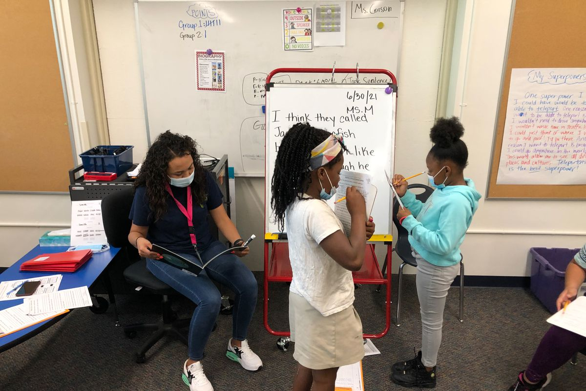 Two young girls work on reading comprehension in front of a small white board as their teacher sits next to them in the classroom. They are all wearing protective masks.