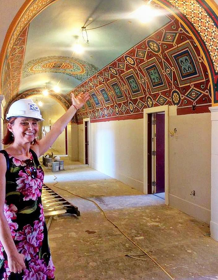 Senior Development Officer Gayle Roberts shows off some of the restored building artwork.