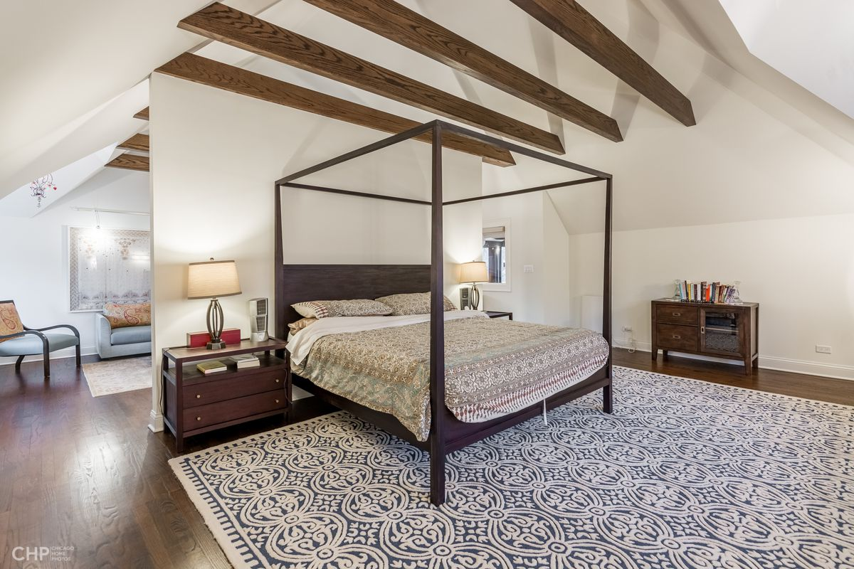 A four-post canopy bed in the center of a spacious bedroom with high ceiling and a large patterned area rug.