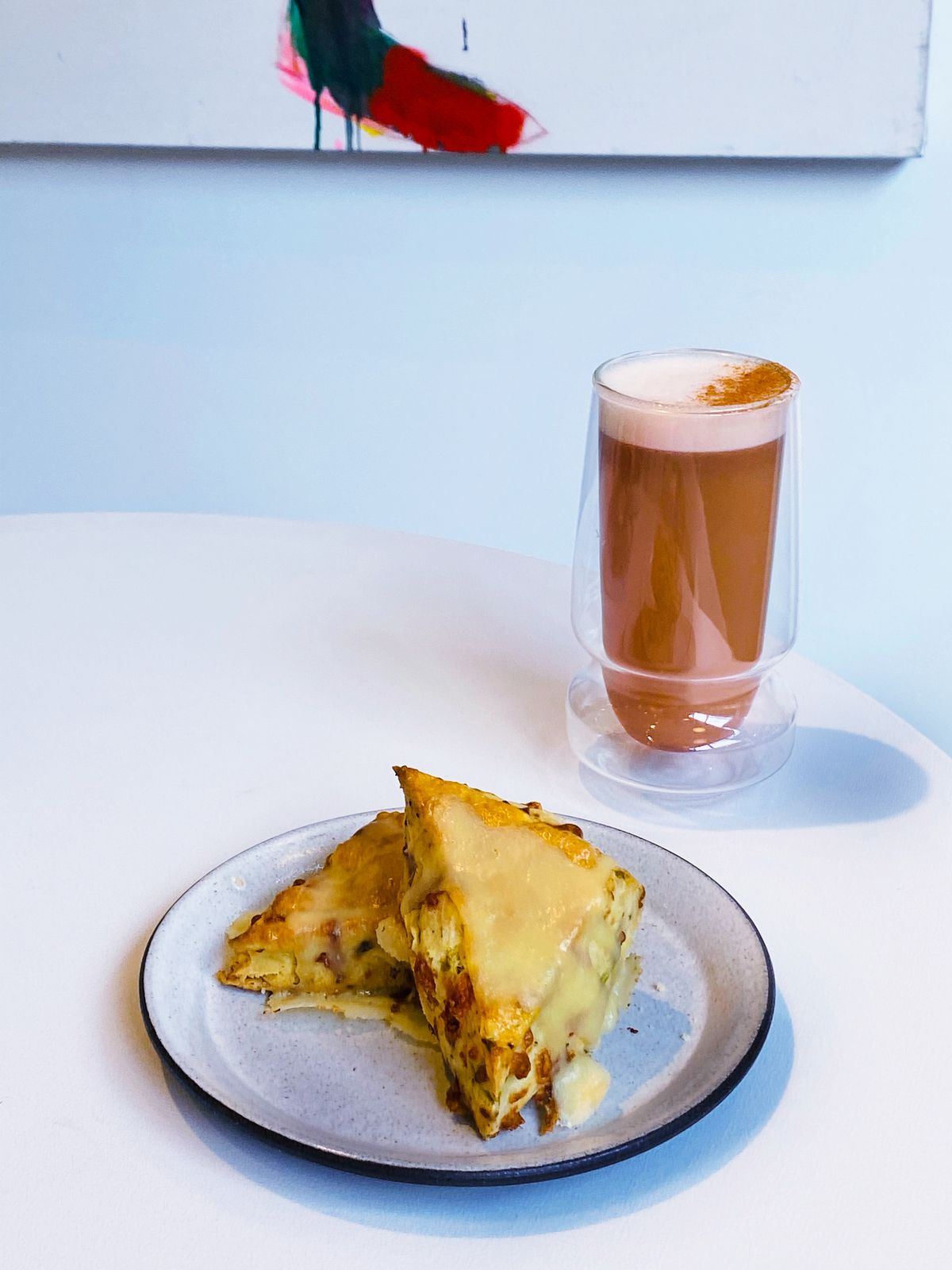 A plate with two scones with yellow melted cheese on top. A glass sits behind the plate with a brownish liquid in it.