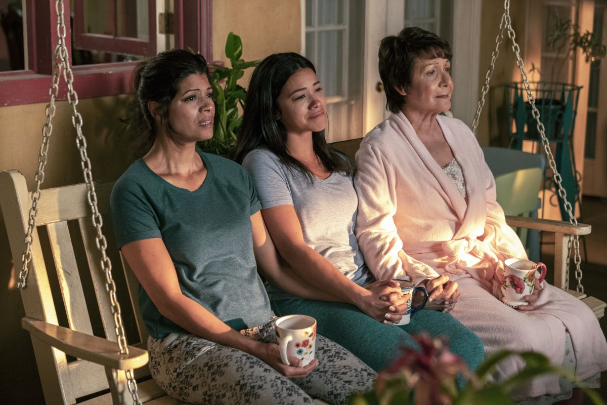 Xo (Andrea Navedo), Jane (Gina Rodriguez), and Alba (Ivonne Coll) sit together in night clothes, crying, on their porch swing