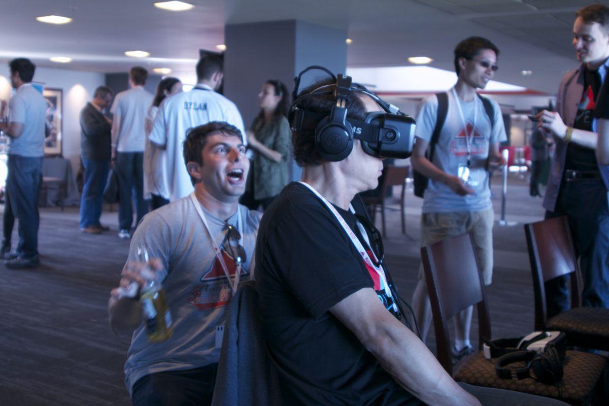 An attendee teases an unwitting VR wearer.