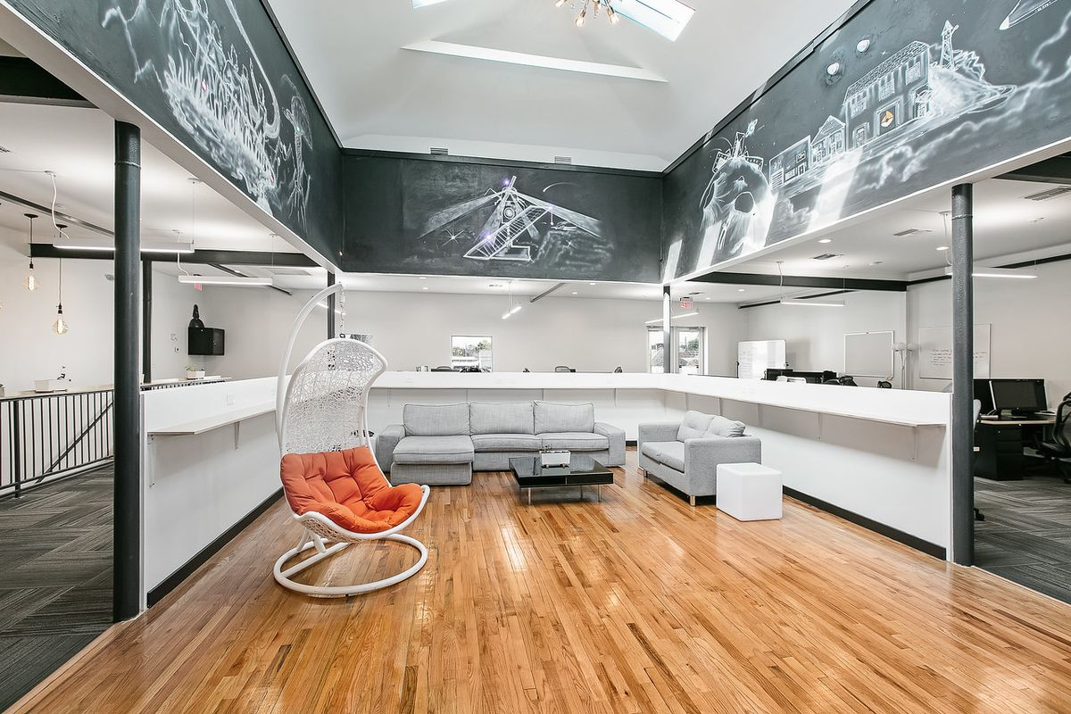 Gray sofas and a curvy chair are surrounded by white half walls and a black-and-white mural.