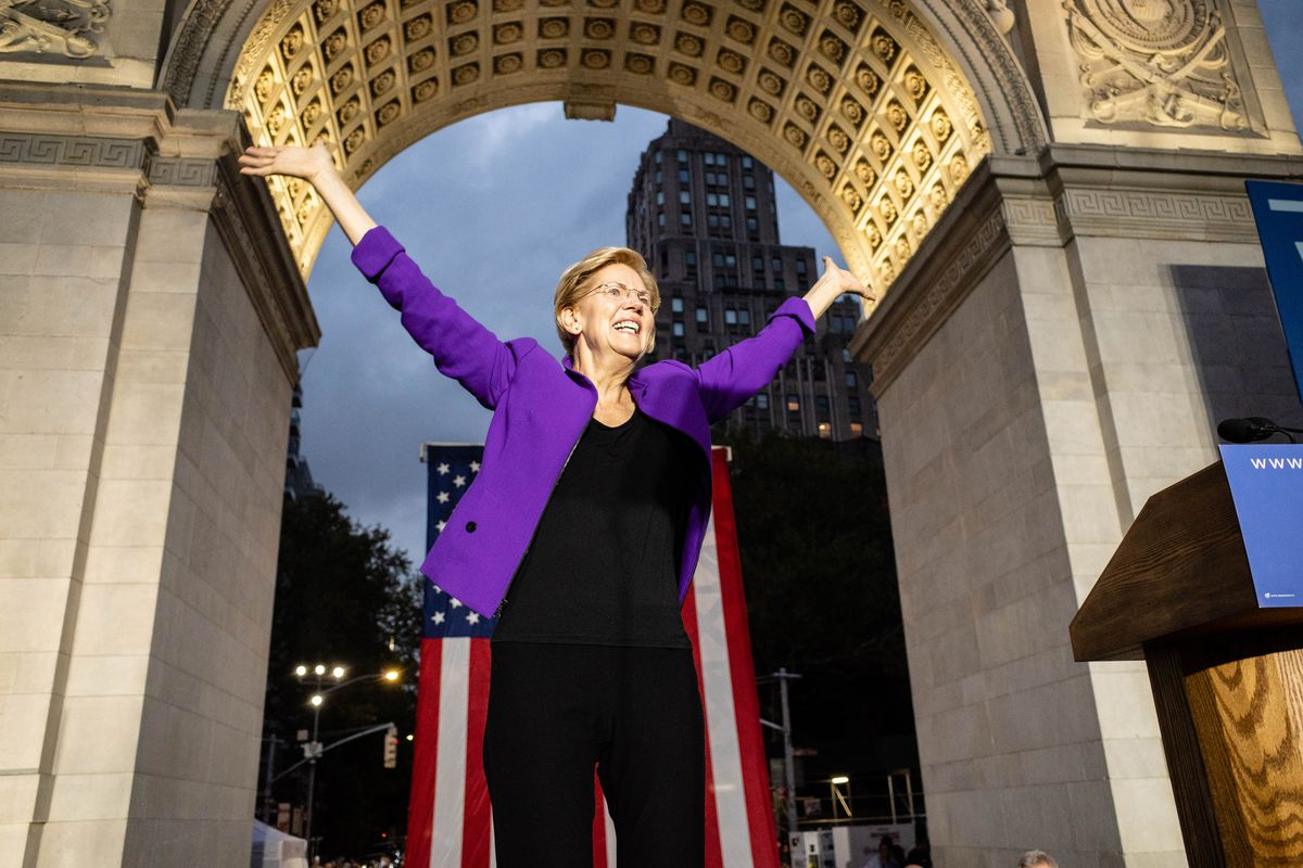 Elizabeth Warren raises her arms and smiles in front of a giant US flag suspended from the arch in New York's Washington Square Park.