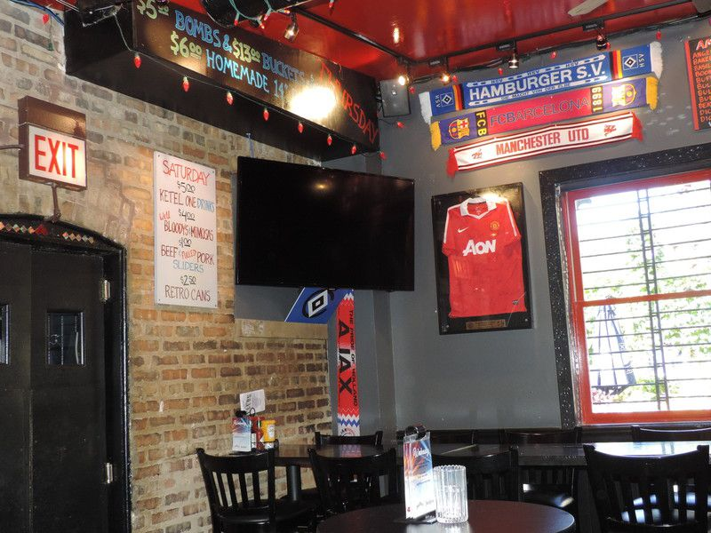 A corner of a sports bar with a television and soccer scarves on the wall.