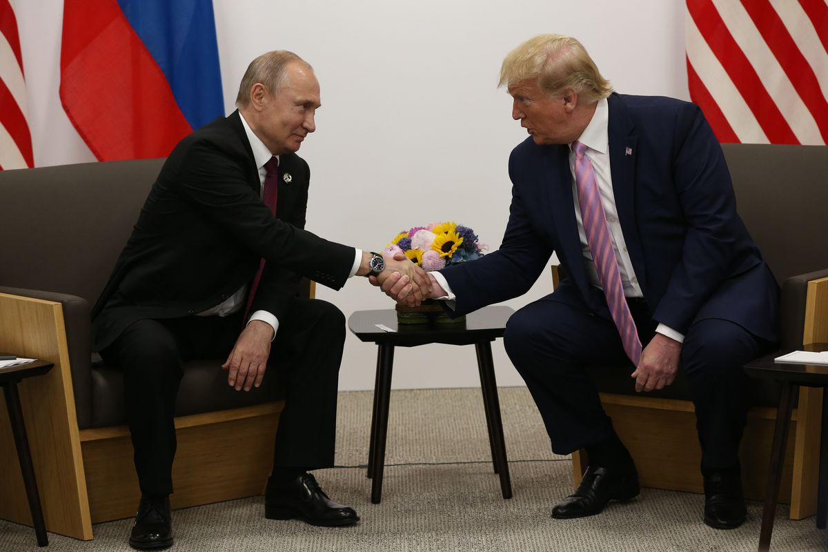 Russian President Vladimir Putin and US President Donald Trump shake hands in front of their nations' flags ahead of a G20 meeting.