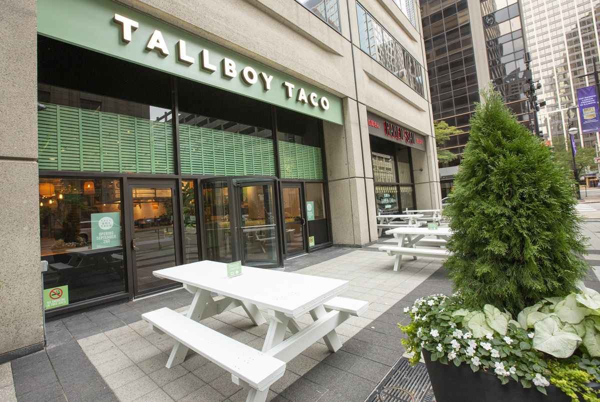 A few white picnic tables sit on a sidewalk outside a restaurant space.