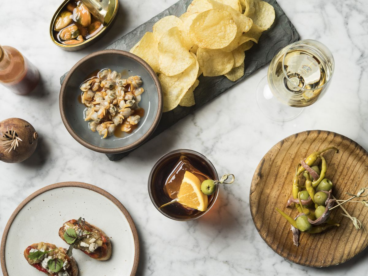 An overhead shot of various tapas and snacks — canned mussels, potato chips, olives, and more — placed upon a marble counter and served alongside a glass of white wine.