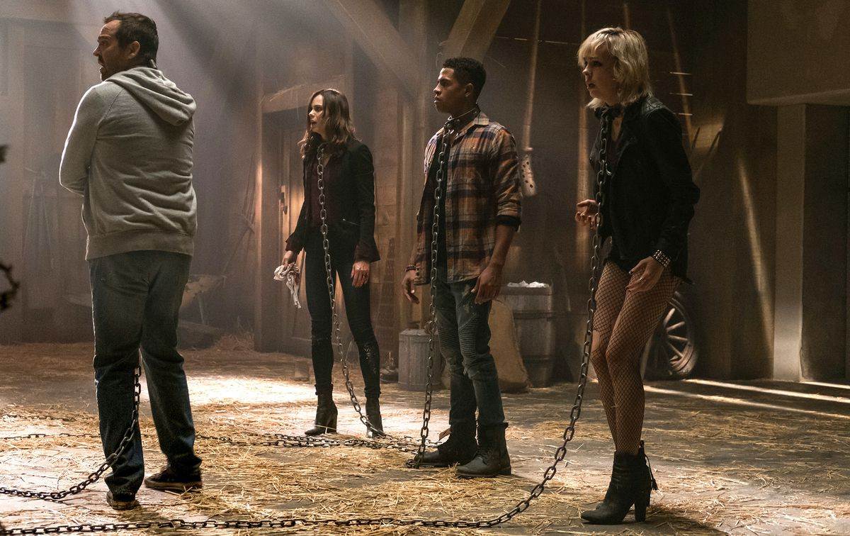 Four potential Jigsaw victims stand in a barn, wearing metal collars and chains, in Jigsaw