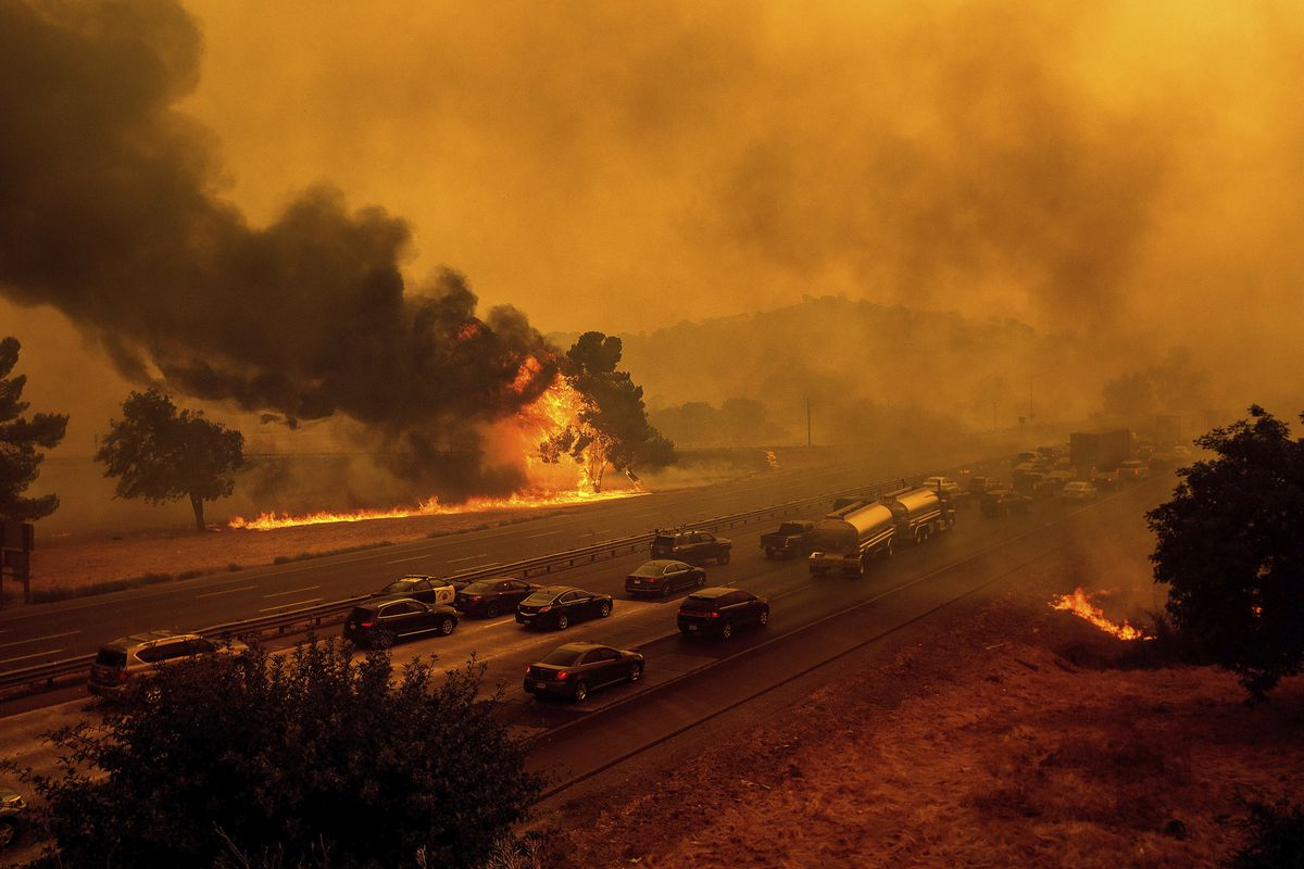 In this Wednesday, Aug. 19, 2020, file photo, flames from the LNU Lightning Complex fires jump Interstate 80 in Vacaville, Calif.