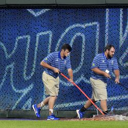 Royals grounds crew members work to clear water after the fountains flooded the field.