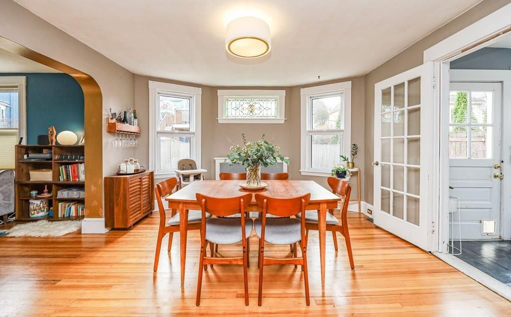 A dining room in between other rooms, with a table and chairs and lots of natural light.