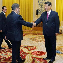 FILE - In this Aug. 29, 2012 file photo, Chinese Vice President Xi Jinping, right, greets Egypt's President Mohammed Morsi during their meeting at the Great Hall of the People in Beijing. Chinese micro-bloggers and overseas websites have come up with all kinds of creative speculation as to why vice president Xi has gone unseen for more than a week. During that span, Xi canceled meetings in Beijing with visiting U.S. Secretary of State Hillary Clinton and Singapore Prime Minister Lee Hsien Loong. Monday, Sept. 10, it was the Danish prime minister's turn.