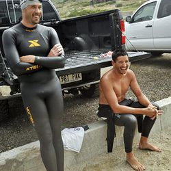 Brian Cleff, left, and John Karren wait for lightning to pass so they can train for a swim marathon at a small lake in Herriman on Aug. 4.