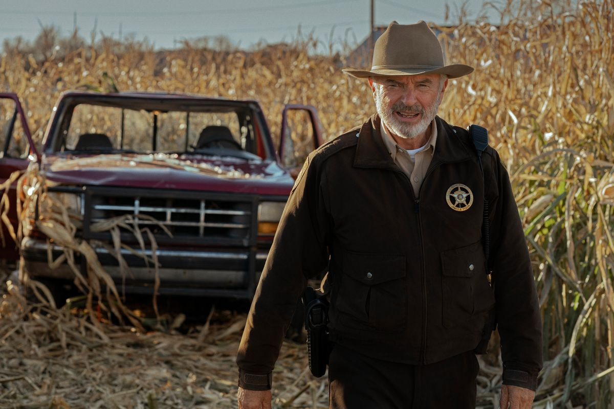 Sam Neill as Sheriff John Bell Tyson stands in a cornfield in the Apple TV Plus show Invasion