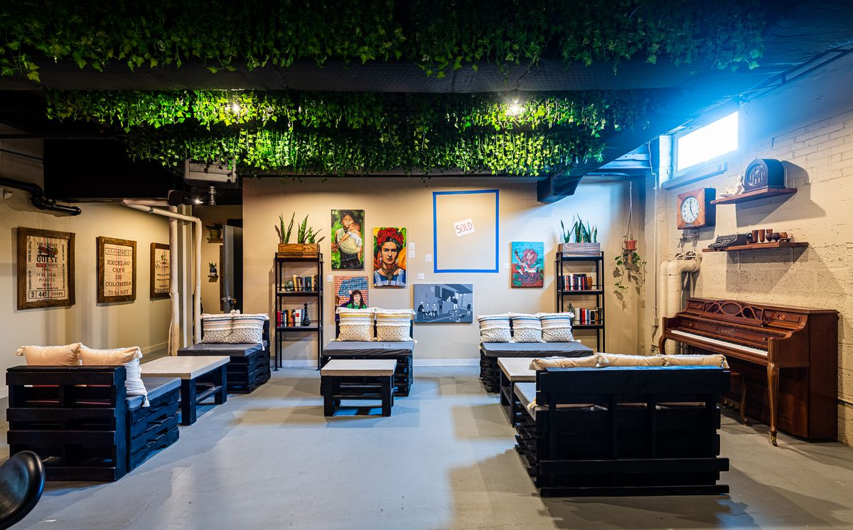 Green plants hang from the ceiling of a room lined with art, white walls, and a brown piano at Chacho's tasting area