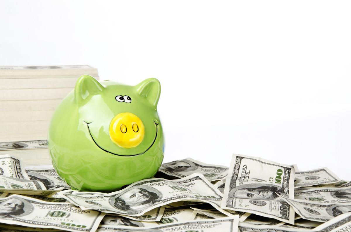 A smiling piggy bank on a pile of hundred-dollar bills