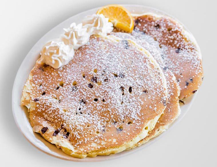 Three large chocolate chip pancakes are spread against a white plate on a white background, topped with powdered sugar, whipped cream, and an orange slice