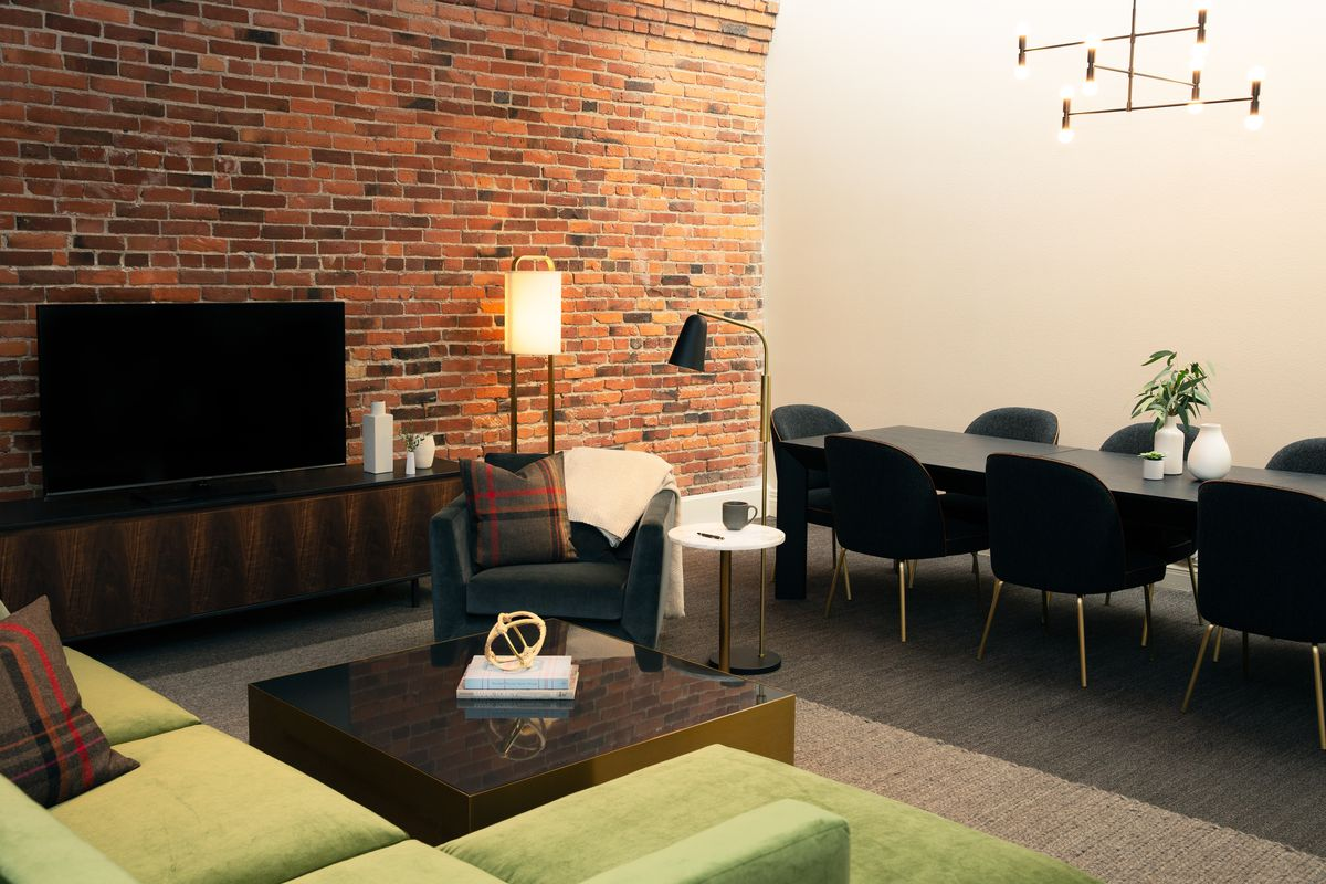 A TV against an exposed brick wall, with a long dining table with a modern fixture above to the right and a green, modern sectional to the left.