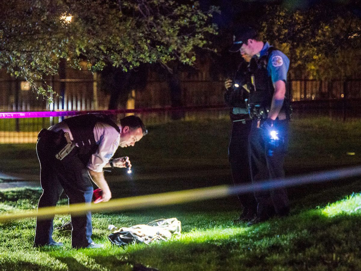 A Chicago Police officer shines a flashlight on clothing found near the scene of a shooting Sunday, May 6, in the 3100 block of West Madison Street | Tyler LaRiviere/Sun-Times