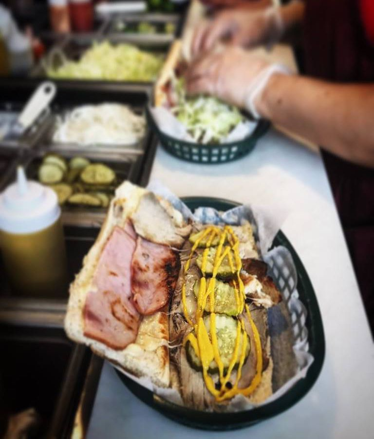 A Cuban sandwich on a counter in a restaurant kitchen, served in a plastic black basket and covered with lots of mustard