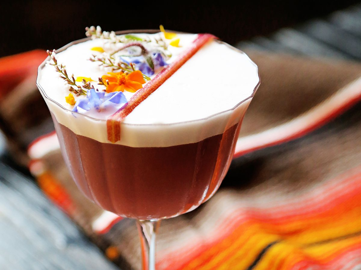 A cocktail topped with edible flowers from the new Traveler bar at 25 Lusk