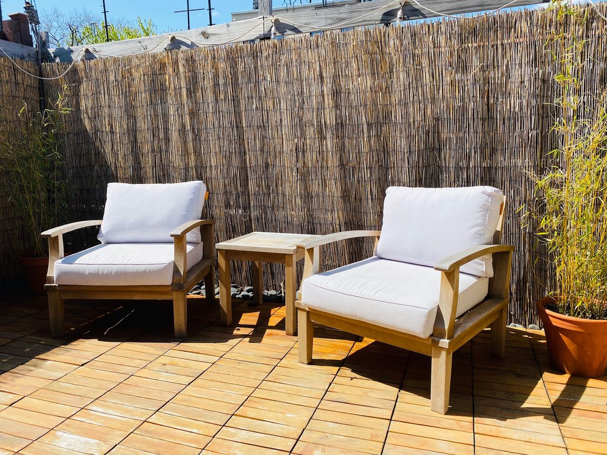 Two chairs with white cushions next to a planter in a backyard.