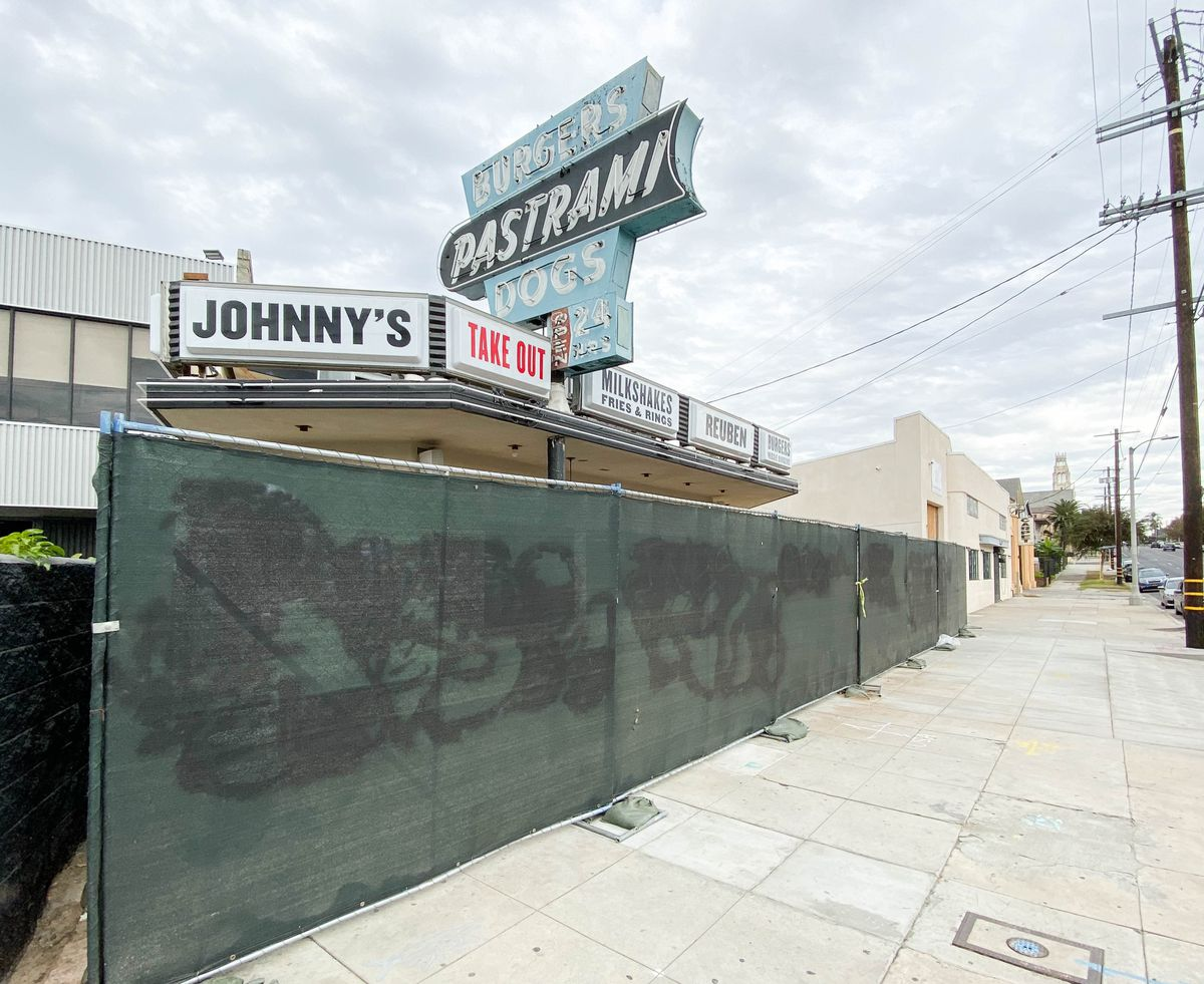 An under-construction restaurant space shown along a wide sidewalk.