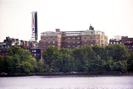 The view of the exterior of a brick dormitory, with a river and lush trees in front of it.