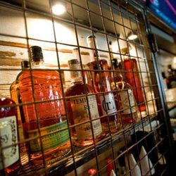 Liquor is displayed inside cages behind the bar