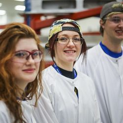 Mychala Sandberg, middle, stands with trainees, Katlynn Simpson, left, and Ben Larsen, right, members of the Utah Aerospace Pathways Program, in the radial room at the Orbital ATK manufacturing facility in Clearfield on Thursday, April 20, 2017.